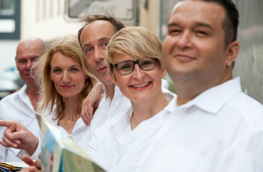 Fünf Menschen mit weißen Hemden und Landkarten.